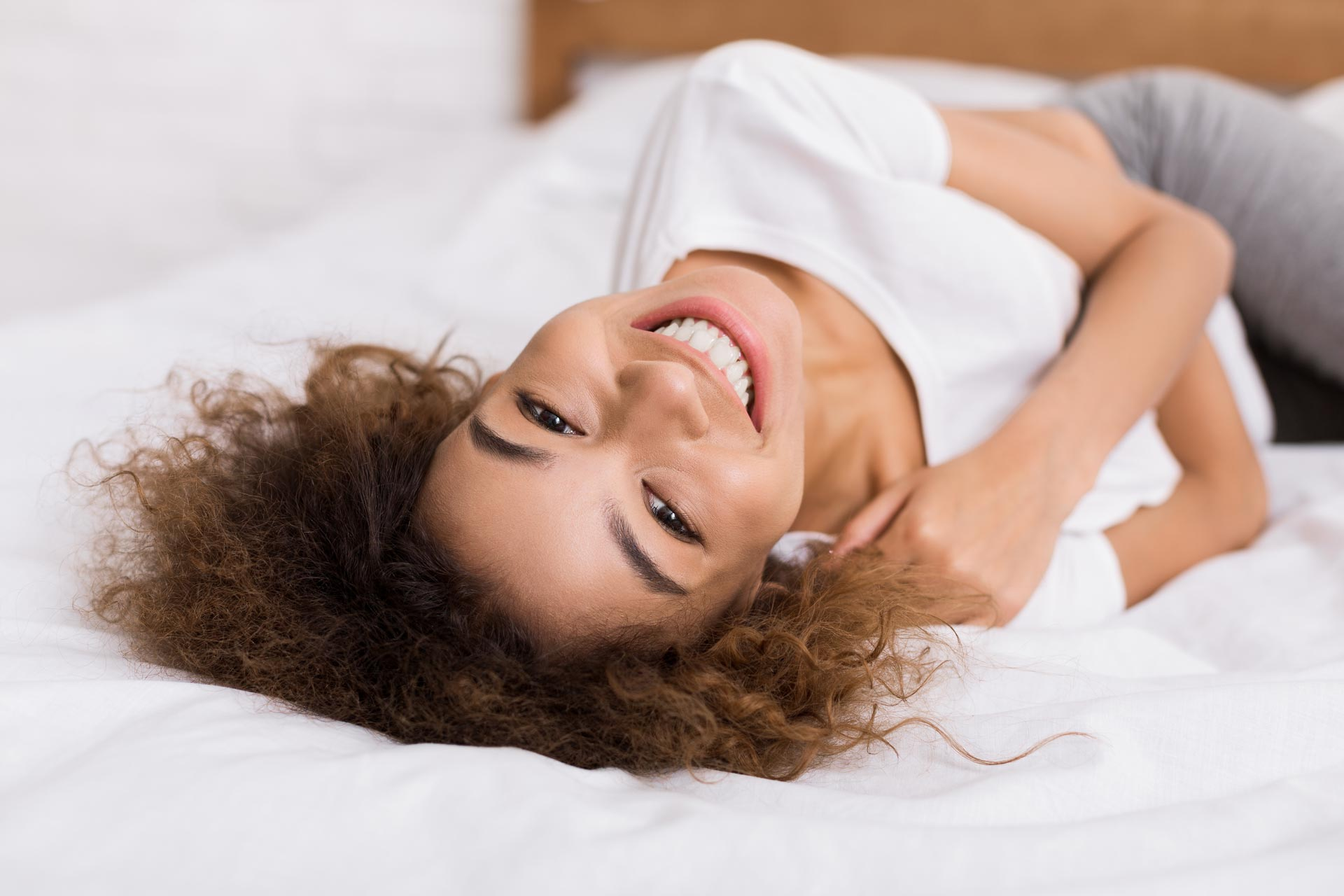 happy-woman-lying-on-bed-and-looking-at-camera-AG4TZW5.jpg